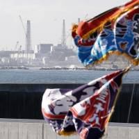 A fisherman's flag billows in wind in January, with the damaged Fukushima No. 1 nuclear power plant seen behind. | KYODO