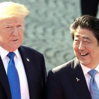 U.S. President Donald Trump speaks with Prime Minister Shinzo Abe as they observe an honor guard at Akasaka Palace in Tokyo during Trump's November visit to Tokyo. | BLOOMBERG