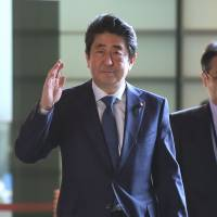 Prime Minsiter Shinzo Abe waves as he arrives at his official residence to attend a Cabinet meeting in Tokyo on Tuesday. | AFP-JIJI