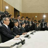 Chief Cabinet Secretary Yoshihide Suga (right) attends a preparation committee meeting Friday at the Prime Minister's Office to help plan the Imperial succession rituals. | KYODO