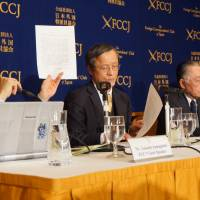 Takashi Yamaguchi, board member at the Japan Society for Cult Prevention and Recovery, holds up a petition sent to the Justice Ministry last week, requesting that the lives of the 12 former Aum members on death row be spared, at the Foreign Correspondents' Club of Japan Monday. | CHISATO TANAKA