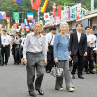 Emperor Akihito and Empress Michiko visit a makeshift shopping center in Minamisanriku, Miyagi Prefecture, on July 23, 2014. The Empress carries a bag made by Asutoro Tech, based in the town, that was devastated by the March 11, 2011, earthquake and tsunami.   KYODO