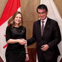 Foreign Minister Taro Kono greets his Canadian counterpart Chrystia Freeland during their talks at a Tokyo hotel on Tuesday. | AFP-JIJI