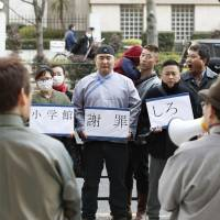 Mongolians living in Japan stage a rally in front of the head office of Shogakukan on Feb. 26 to protest a comic it published which included an image of Genghis Khan with a crude sketch of male genitalia across his forehead. | KYODO