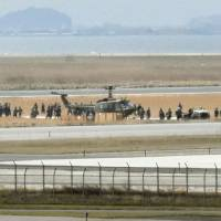 People surround a Ground Self-Defense Force helicopter after it made an emergency landing at Yonago Airport in Tottori Prefecture on Thursday. | KYODO