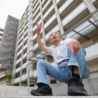 An elderly man sits in front of public housing designated for 'disaster recovery' in Sendai in September. | KYODO