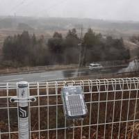 A Geiger counter from the Safecast nongovernmental organization outside the Fukushima Prefecture town of Okuma measures radiation from the nearby Fukushima No. 1 nuclear power plant on March 5. | AFP-JIJI