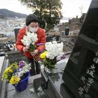 A woman visits the grave of her husband, who was swept away by tsunami on March 11, 2011, in Otsuchi, Iwate Prefecture, on Sunday. | KYODO