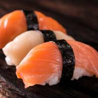 Squid and salmon sushi is arranged for a photo. Seafood company Nippon Suisan Kaisha Ltd. has developed alternatives for Japanese flying squid and imported salmon, for use in sushi and sashimi, as prices surge. | GETTY IMAGES