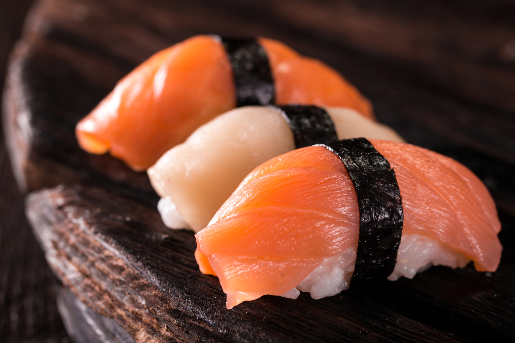 Squid and salmon sushi is arranged for a photo. Seafood company Nippon Suisan Kaisha Ltd. has developed alternatives for Japanese flying squid and imported salmon, for use in sushi and sashimi, as prices surge.   GETTY IMAGES