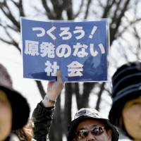 A protester holds up a sign saying 'Let's create a society without nuclear power plants!' in front of the Genkai plant in Genkai, Saga Prefecture, on Friday as its No. 3 reactor was put back online. | KYODO