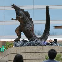 People look up at a new Godzilla statue, unveiled on Thursday at a shopping mall in central Tokyo. | KYODO