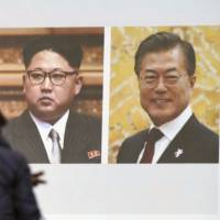 A woman walks past a public TV screen showing a news clip with the photos of North Korean leader Kim Jong Un (left) and South Korean President Moon Jae-in in Tokyo on Wednesday. | AP