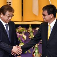 South Korea's National Intelligence Service chief Suh Hoon (left) shakes hands with Foreign Minister Taro Kono before their meeting in Tokyo Monday. | AP