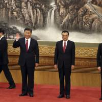 Chinese Premier Li Keqiang stands beside President Xi Jinping along with other members of the Chinese Politburo at the Great Hall of the People in Beijing on Oct. 25. | AP