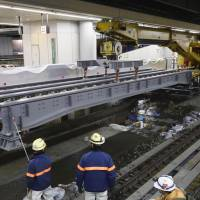 Construction workers put girders in place for the maglev track at Shinagawa Station in Tokyo in November. | KYODO