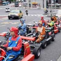 People ride go-karts on a public road in Minato Ward, Tokyo, in March 2017. Their faces are blurred for privacy reasons. | KYODO