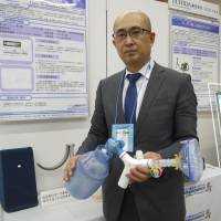 Takashi Sekine, president of Carter Technologies Inc., displays a device that helps ALS patients practice deep breathing and expand their lung capacity. | TOMOKO OTAKE