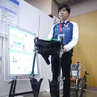 Katsuyuki Hara, a researcher at Uchida Co., says the firm's motorless exoskeletons can help people who are paralyzed from the waist down experience the fun of walking. | TOMOKO OTAKE
