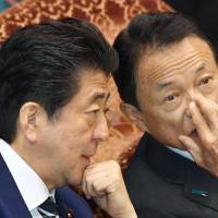 Prime Minister Shinzo Abe speaks with Finance Minister Taro Aso on Thursday at an Upper House budget committee. | KYODO