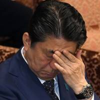 Prime Minister Shinzo Abe rubs his forehead while attending an Upper House Budget Committee session at the Diet in Tokyo on Wednesday. | AFP-JIJI