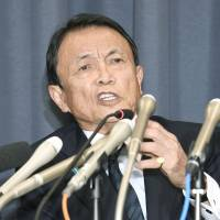 Finance Minister Taro Aso speaks at a news conference at the ministry in Tokyo's Kasumigaseki district on Friday. | KYODO