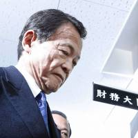 Finance Minister Taro Aso enters his office at the ministry on Monday. | KYODO