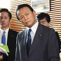 Finance Minister Taro Aso listens to a reporter's question after a Cabinet meeting at the Prime Minister's Office on Tuesday. | KYODO