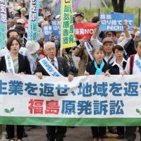 A group of plaintiffs walk in front of Fukushima District Court in October 2017. The secretariat of the Nuclear Regulation Authority will increase its number of legal staff from this spring to deal with lawsuits.   KYODO