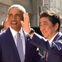 Former U.S. President Barack Obama and Prime Minister Shinzo Abe pose in front of a sushi restaurant in Tokyo's Ginza shopping district on Sunday. Earlier that day, Obama spoke on the North Korean nuclear crisis at a packed Tokyo hall. | REUTERS