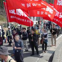 People take part in an anti-nuclear protest Wednesday in the town of Oi, Fukui Prefecture, after Kansai Electric Power Co. restarted the No. 3 reactor at its plant there earlier in the day. | KYODO