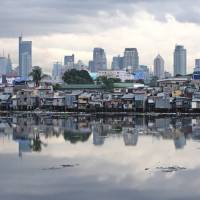 Manila's business and residential districts are seen reflected in a river. The number of Japanese visitors to the Philippines has been on the rise in recent years thanks to their desire to study English at an affordable cost. | BLOOMBERG