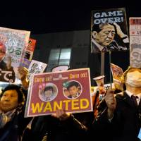 Protesters blast Prime Minister Shinzo Abe during a rally near his office Monday evening, hours after the Finance Ministry admitted to secretly doctoring documents at the center of a cronyism scandal linked to Abe and his wife. | AFP-JIJI