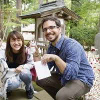A foreign tourist is delighted with a maneki-neko doll at Gotokuji Temple located along Tokyu Corp.'s Setagaya Line in Tokyo. | VIA KYODO