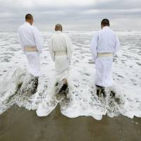 Buddhist priests enter the sea Sunday in the Tairausuisho district of Iwaki, Fukushima Prefecture, to pray for those who were swept away by the tsunami that scoured the area on March 11, 2011. | KYODO