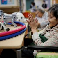 A resident claps to call Aibo, a robotic dog, at Shintomi nursing home in Tokyo. | REUTERS