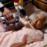 Yoichi Suzuki shows Aibo to his bed-ridden mother at his house in Takahagi, Ibaraki Prefecture, on Feb. 6. | REUTERS