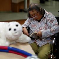 A resident reads a book during a session with Paro, a robotic seal, at the Shintomi nursing home in Tokyo. | REUTERS