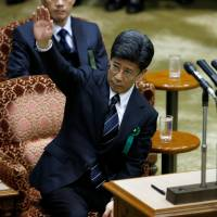 Former National Tax Agency chief Nobuhisa Sagawa, a key figure in a cronyism scandal that has sparked a political crisis for Prime Minister Shinzo Abe, raises his hand as he testifies at the Upper House of the Diet in Tokyo on Tuesday.   REUTERS