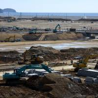 Work to elevate land devastated by tsunami in March 2011 progresses in Rikuzentakata in February. Millions of tons of soil brought in from higher ground is being used to raise the city's center by as much as 12 meters to mitigate future disasters. | SATOKO KAWASAKI