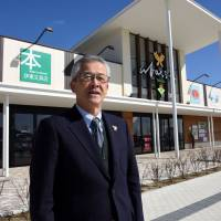 Takashi Ito, head of a business cooperative in Rikuzentakata, Iwate Prefecture, says he hopes the Abasse Takata shopping mall (background) built last year will become a place where what's left of his community can gather again. | SATOKO KAWASAKI
