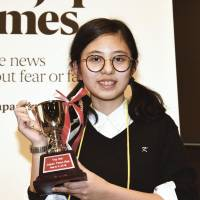 Hanna Yoshida from K. International School Tokyo poses with her trophy on Saturday after winning the ninth Japan Times Bee at the newspaper's headquarters in Tokyo. Yoshida correctly spelled insubordinate to secure the right to represent Japan at the finals of the Scripps National Spelling Bee in Washington in May. | SATOKO KAWASAKI