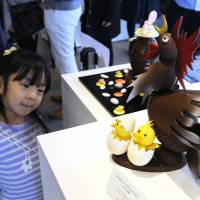 A young child looks at a chocolate cake during an Easter festival in Tokyo's Daikanyama neighborhood in March 2016. | KYODO