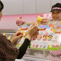 A retail assistant hands a customer limited edition Easter goods in March 2015. | KYODO