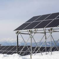 Here comes the sun: Snow sits on the ground around solar panels at Aizu Electric Power Co.'s Oguni power plant in Kitakata, Fukushima Prefecture. The panels are elevated on scaffolding to raise them above the snow during winter. | CHRISTINA SJOGREN
