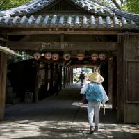 One down: A pilgrim, known as o-henro-san, walks through the gates of Ishiteji, temple number 51 of 88 on the Shikoku Pilgrimage. | CHRISTINA SJOGREN