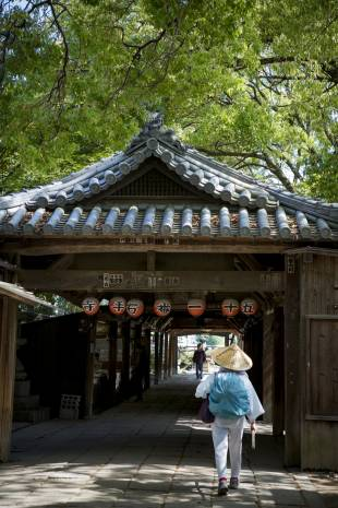 One down: A pilgrim, known as o-henro-san, walks through the gates of Ishiteji, temple number 51 of 88 on the Shikoku Pilgrimage.