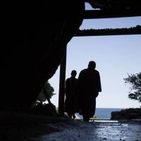 Monks leave the cave on Cape Muroto, Kochi Prefecture, where the Buddhist monk Kobo Daishi achieved enlightenment in 804. | CHRISTINA SJOGREN