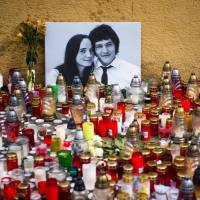 Hundreds of candles are placed in front of a portrait of investigative journalist Jan Kuciak and his girlfriend Martina Kusnirova in Bratislava. The couple were found murdered on Monday at their home in Velka Maca, Slovakia. | AFP-JIJI