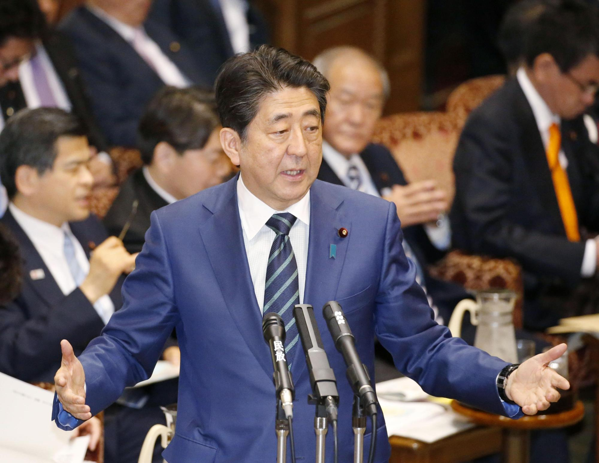 Prime Minister Shinzo Abe speaks at the  Upper House Budget Committee on March 1, where he promised the government would look again at the impact of the discretionary work system on people's work hours. | KYODO